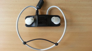 Der MP3-Player eingeklick in der Dockingstation. Das schwarze Gummi unten am Kopfhörerkabel dient dazu, das Kabel so auf Spannung zu bringen, dass es 100%ig fest sitzt.